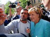 A migrant takes a selfie with German Chancellor Angela Merkel outside a refugee camp near the Federal Office for Migration and Refugees after registration at Berlin's Spandau district, Germany September 10, 2015. REUTERS/Fabrizio Bensch