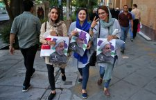 In this picture taken on Wednesday, May 17, 2017, supporters of Iranian President Hassan Rouhani hold his posters during a street campaign ahead the May 19 presidential election in downtown Tehran, Iran. Iranian President Hassan Rouhani staked his political future on opening Iran ever so slightly to the outside world and overcoming hard-liners' opposition to secure a historic nuclear deal in exchange for relief from crippling sanctions. (AP Photo/Vahid Salemi)