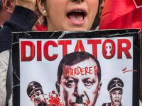 A young British Alevi protester holds a poster showing President Erdogan with blood dripping from his face and the word 'Murderer' aross his forehead at London protest in solidarity with those kiled in Ankara bombings.