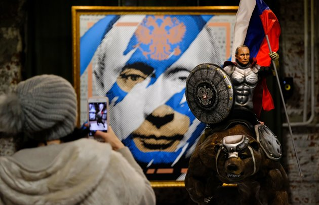 """A visitor takes a picture of a sculpture depicting Russian president Vladimir Putin at the """"SUPERPUTIN"""" exhibition at UMAM museum in Moscow on December 6, 2017. / AFP PHOTO / Yuri KADOBNOV / RESTRICTED TO EDITORIAL USE - TO ILLUSTRATE THE EVENT AS SPECIFIED IN THE CAPTION        (Photo credit should read YURI KADOBNOV/AFP/Getty Images)"""