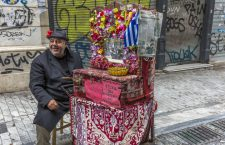 Athens, Greece - April 9th, 2015. An organ grinder plies his trade against the backdrop of the prevailing economic crisis.