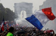 Supporters wave French national flags as they gather on the Champs-Elysees avenue near the Arch of Triumph (Arc de Triomphe) in Paris on July 16, 2018 during the parade of French national football team for celebrations after France won the Russia 2018 World Cup final football match on the previous night. (Photo by Geoffroy VAN DER HASSELT / AFP)        (Photo credit should read GEOFFROY VAN DER HASSELT/AFP/Getty Images)
